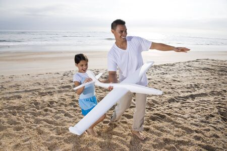 Hispanic father and 9 year old daughter having fun with toy plane on beach
