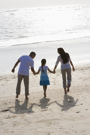 Rear view of Hispanic family with 9 year old girl holding hands walking on beach photo