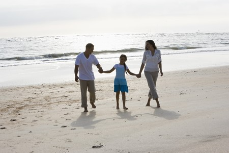 9 year old girl: Hispanic family with 9 year old girl holding hands walking on beach