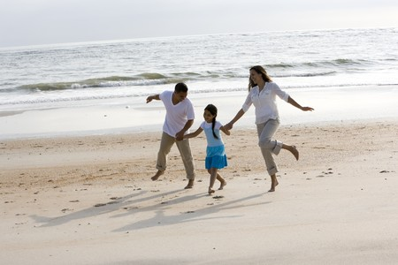 Hispanic family with 9 year old girl holding hands skipping on beach