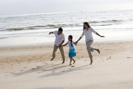 Hispanische familie met 9 jaar oud meisje hand in hand overslaan op het strand