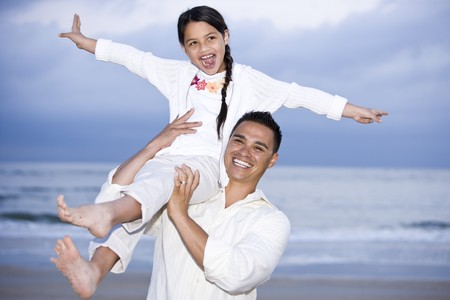 Happy Hispanic dad and 9 year old daughter having fun on beach photo