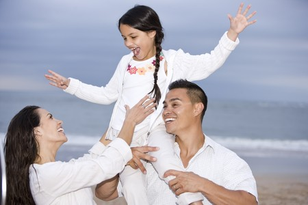 Happy Hispanic family and 9 year old daughter having fun on beach photo