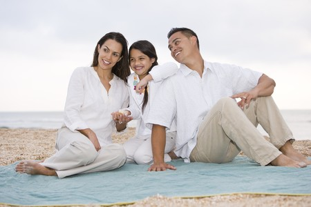 Hispanic family with 9 year old daughter on beach blanket