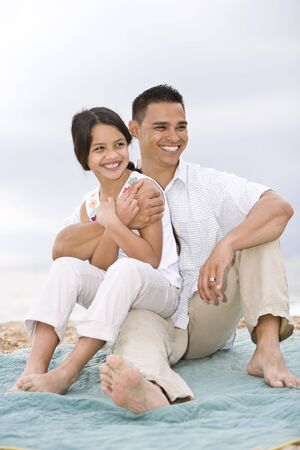 Hispanic father with 9 year old daughter on beach blanket photo