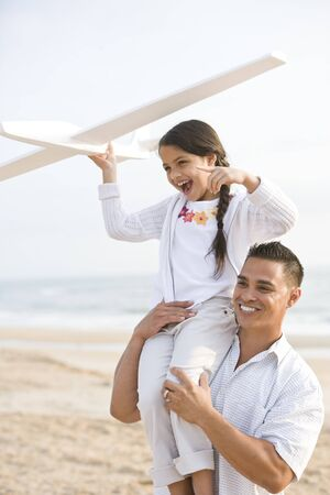 9 year old girl: Hispanic father and 9 year old girl having fun on beach playing with model plane