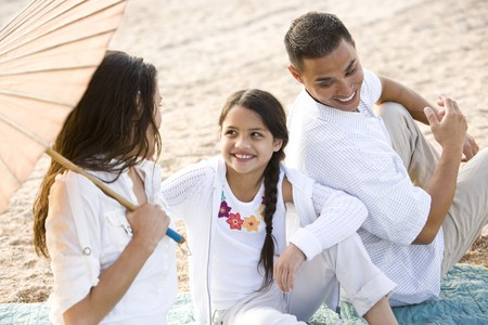 High angle view of happy Hispanic family with 9 year old daughter on beach photo