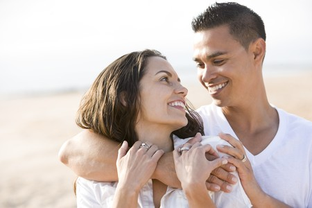 Close up of affectionate Hispanic couple on beach looking at each other photo