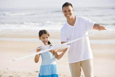 9 year old: Hispanic 9 year old girl and father playing with toy airplane on beach