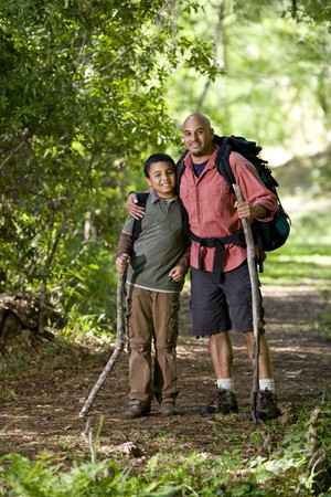 Father and 10 year old son hiking on trail in woods photo