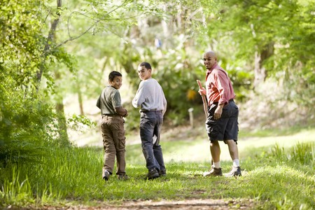 Rear view of father and two sons hiking on trail in woods photo