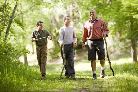 Father and two sons hiking on trail in woods and talking Stock Photo