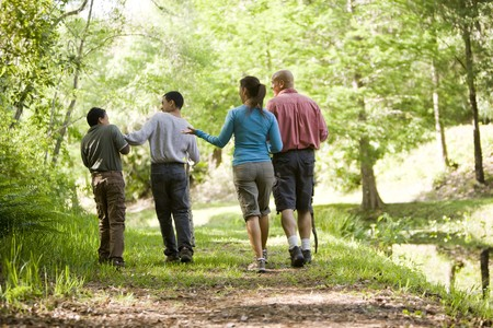 explore: Rear view of Hispanic family walking along trail in park Stock Photo