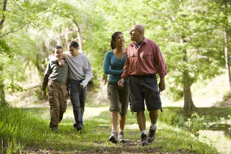 Happy Hispanic family with two boys walking along trail in park