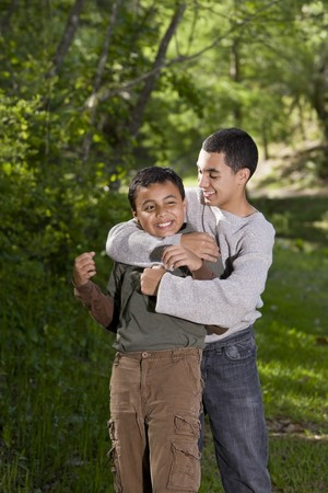 horseplay: Hispanic teenage boy playing with and teasing brother