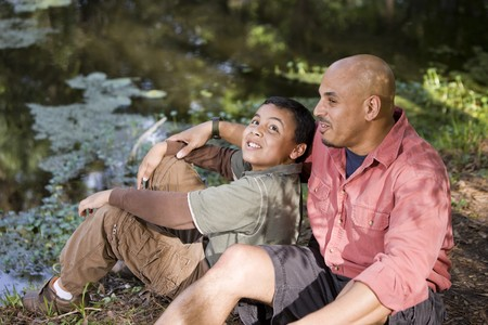 Portrait Hispanic father and son outdoors by pond having conversation photo
