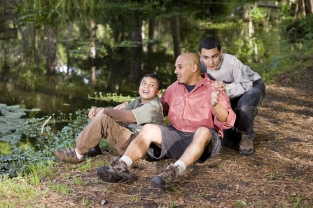 Portrait Hispanic father and sons outdoors by pond having conversation Stock Photo - 7319124