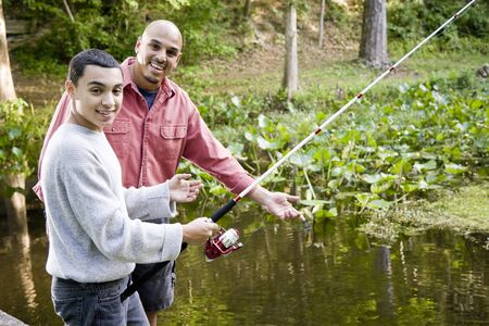 Hispanic 14 year old teen boy and father fishing in pond