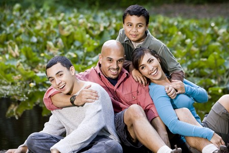 Portrait of happy Hispanic family with two boys outdoors Banco de Imagens