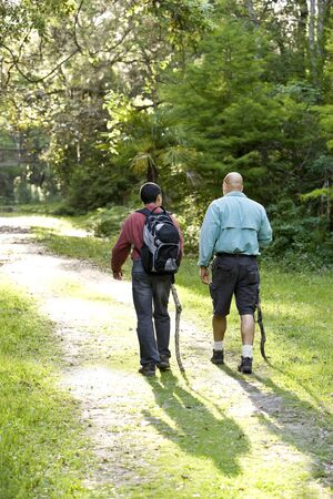 Rear view father and teenage son hiking on path in woods photo