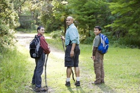Rear view of Hispanic father and two sons hiking on path in woods photo