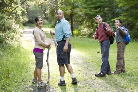 Hispanic family with two boys hiking in woods on trail photo
