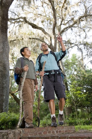 Hispanic father and son hiking in park enjoying nature photo