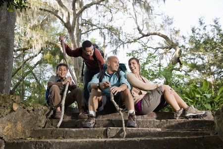 Hispanic family with backpacks hiking in park resting photo