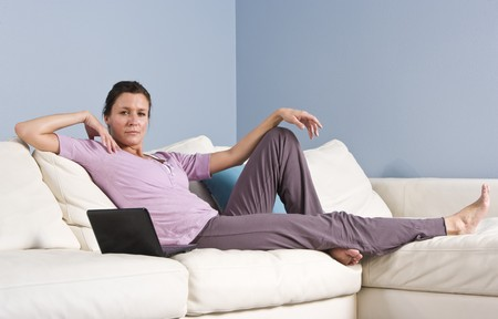 woman on couch: Portrait of mid-adult woman relaxing on couch at home with laptop