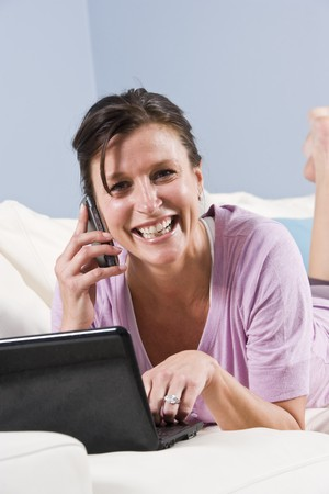 Modern woman relaxed on couch with mobile phone and laptop computer photo