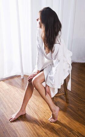 window curtains: Beautiful brunette woman wearing bathrobe looking out window