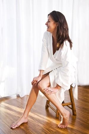 Beautiful brunette woman wearing bathrobe sitting on stool photo