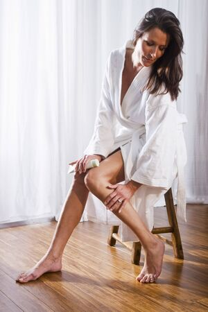 Beautiful brunette woman wearing bathrobe applying lotion to legs photo