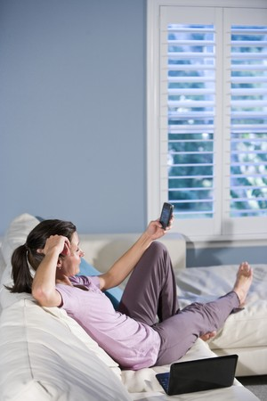 Woman relaxing on couch reading text messages on mobile phone photo