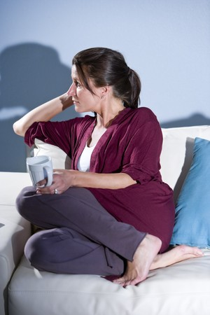 woman on couch: Pensive mid-adult woman drinking coffee thinking on couch at home Stock Photo