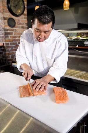 スライス サーモン寿司生の魚のレストランの日本人シェフ