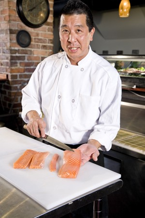 Japanese chef in restaurant slicing raw fish for salmon sushi