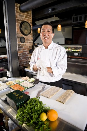 Japanese chef in restaurant with sushi ingredients ready to prepare rolls Stock Photo