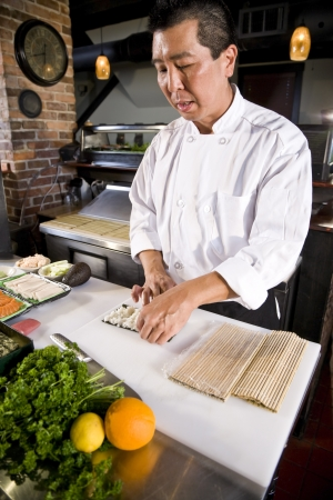 Professional Japanese chef in restaurant making sushi rolls photo