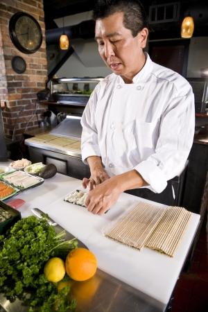 Professional Japanese chef in restaurant making sushi rolls Stok Fotoğraf