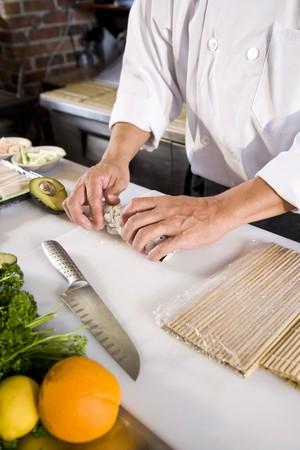 Professional Japanese chef in restaurant making sushi rolls photo