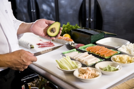 Japanese chef in restaurant with fresh ingredients for making sushi rolls photo