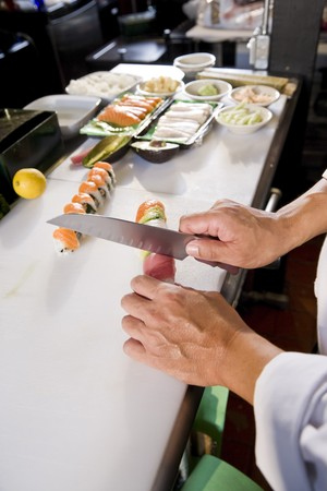 Chef in Japanese restaurant slicing sushi rolls, fresh ingredients on counter
