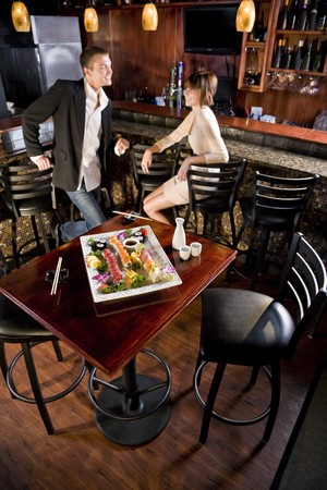 Platter of sushi on table in Japanese restaurant, couple at bar counter in background photo