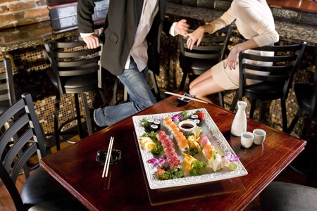 Platter of sushi on table in Japanese restaurant, couple at bar counter in background Stock Photo