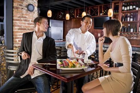 요리사와 이야기하는 일본 레스토랑에서 초밥을 먹고있는 부부