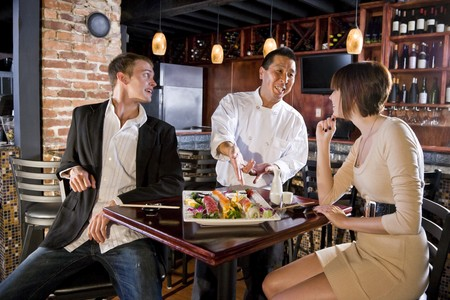 diners: Couple having sushi in Japanese restaurant talking with chef