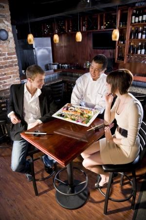 젊은 부부에게 초밥의 플래터를 제공하는 일본 스시 요리사