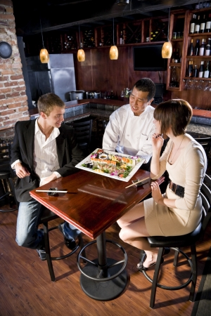 Japanese sushi chef serving platter of sushi to young couple
