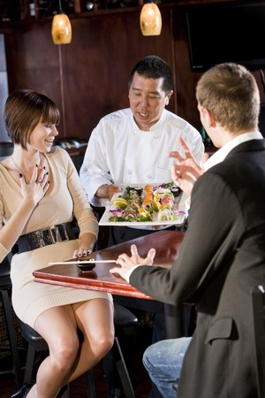 waiter serving: Japanese sushi chef serving platter of sushi to young couple